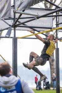 Athlet schwingt von einer Querstange des Hindernisses zur nächsten