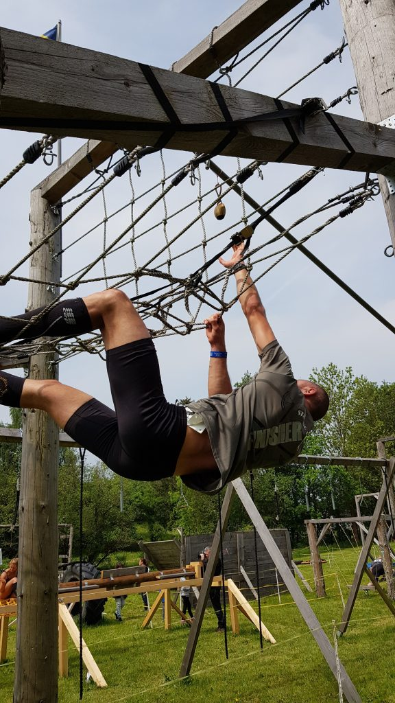 Athlet klettert an Cargo-Netz hinauf