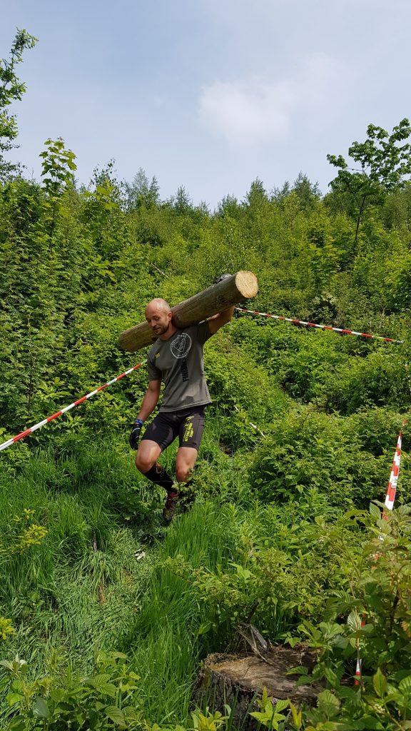 Athlet trägt Baumstamm einen Hang hinunter