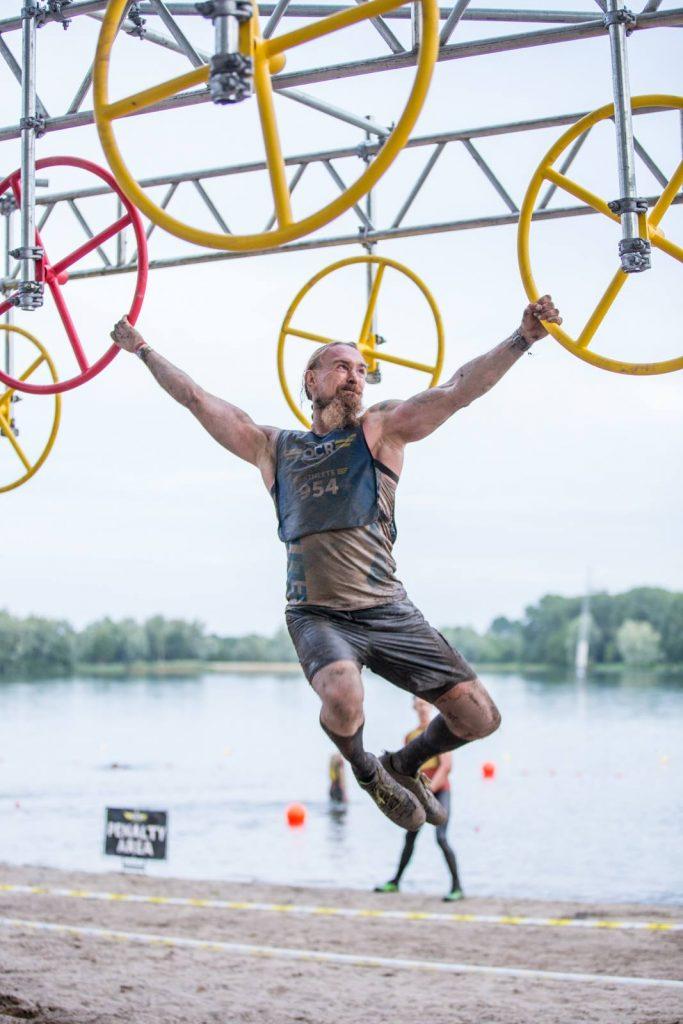 Athlet hängt an zwei schwingenden Rädern