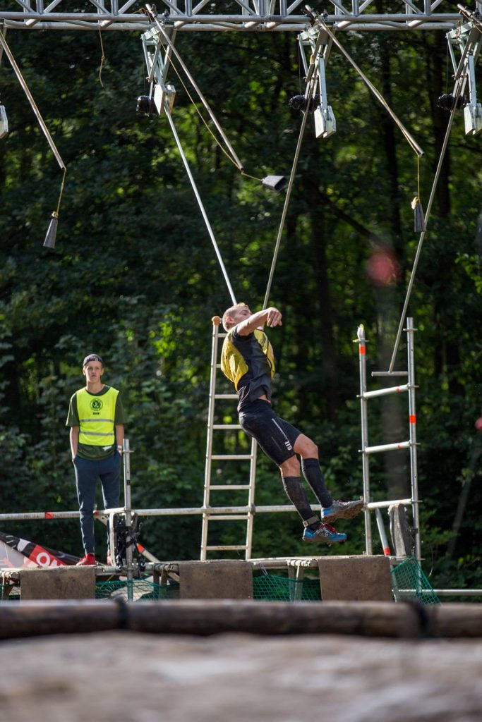 Athlet schwingt an einer beweglichen Stange und schlägt eine Glocke