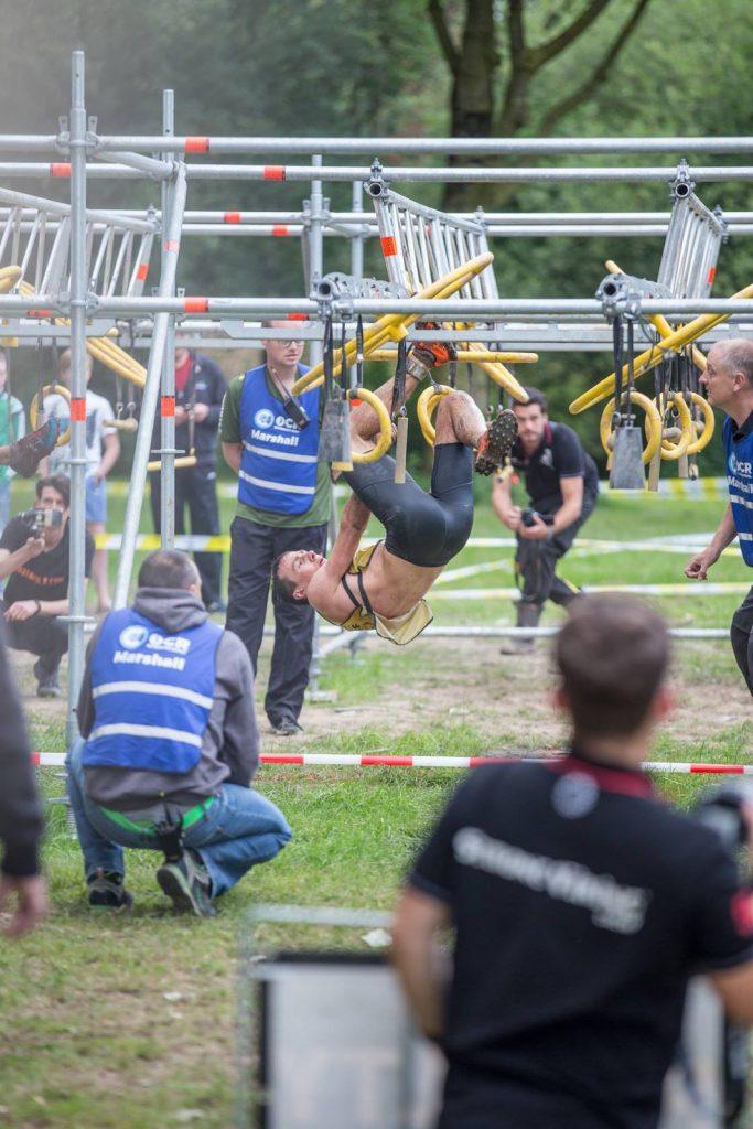 Vier Marshalls achten darauf, dass der Athlet am Hindernis nicht den Boden berührt