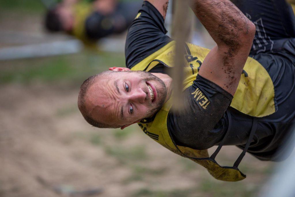 Kritische Blicke eines Athleten in Richtung Boden am Hangelhindernis