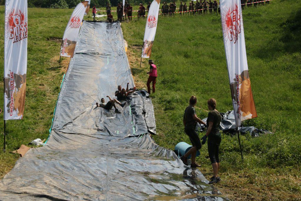 Sportler rutschen auf einer Plane den Hang hinunter