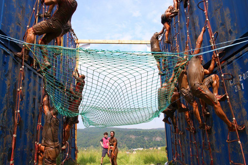 Sportler klettern über übereinandergestapelte Überseecontainer