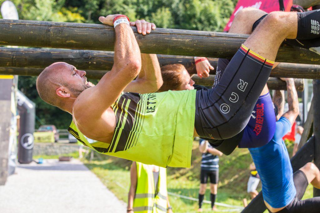 Sportler hängt an quer liegendem Balken