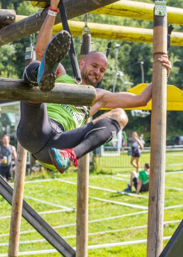 Athlet überwindet ein Hindernis aus verschiedenen Balken