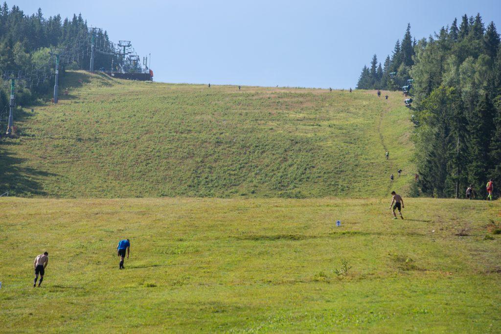 Athleten laufen eine steile Skipiste hinauf